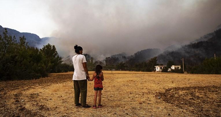 Žena i ćerka gledaju kako se dim nadvija nad domom